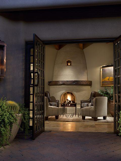 Doors opening to a beautiful fireplace.